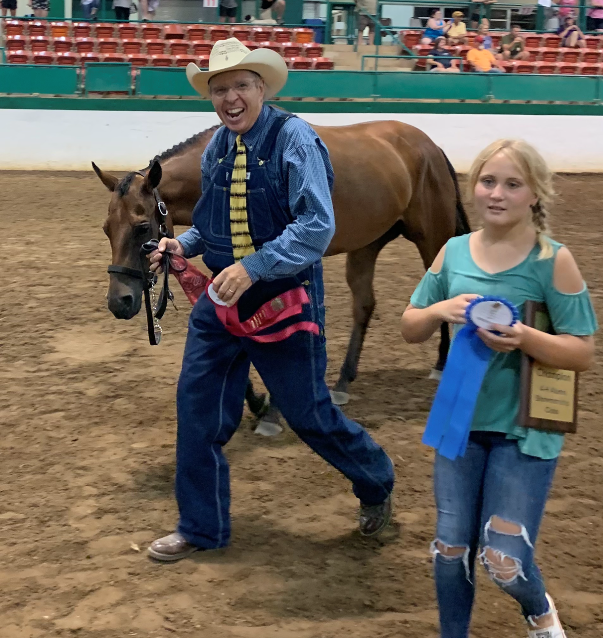 Girl holding award with man leading a horse in background